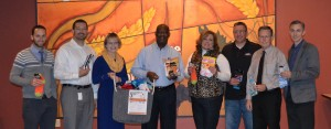 Socktober sponsors turn in socks to United Way President and CEO Lester Lattany.